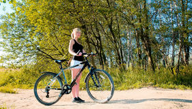 Woman standing and holding bicycle in a park. Royalty Free Stock Photography
