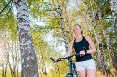 Woman standing and holding bicycle in a park. Royalty Free Stock Image