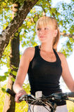 Woman standing and holding bicycle in a park. Stock Photography