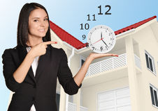 Woman standing and holding clock on pointing at Stock Images