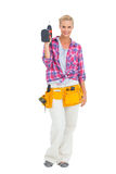 Woman standing holding a drill Stock Image
