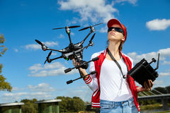 Woman is standing and holding drone Stock Photos