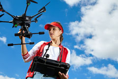 Woman is standing and holding drone Royalty Free Stock Photo