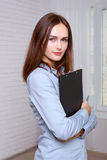 Woman standing holding a folder in half turn Royalty Free Stock Image