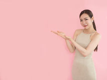 Woman standing holding her hand showing something on pink backgr Royalty Free Stock Images