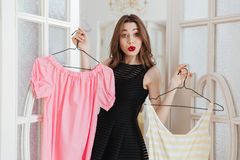 Woman standing indoors choosing between two dresses. Royalty Free Stock Photography