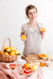 Woman standing indoors and holding citruses in hands Stock Photo