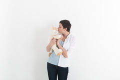 Woman standing and kissing her white and lovely plush cat. Royalty Free Stock Image
