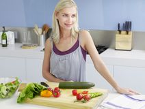 Woman Standing At Kitchen Counter Stock Photo