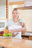Woman standing in the kitchen with her baby on her arms Stock Photos