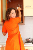 Woman standing in kitchen and opens сupboard Stock Photos