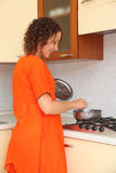 Woman standing in the kitchen and prepare food Royalty Free Stock Images