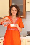 Woman standing in  kitchen and water in cup Royalty Free Stock Images