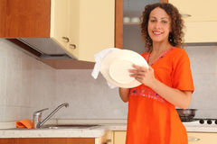 Woman standing in kitchen and wipes clean utensils Royalty Free Stock Photo