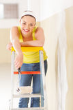 Woman standing on ladder. Happy young woman standing on ladder with painting roller royalty free stock images
