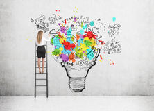 Woman standing on a ladder and drawing a large and colorful light bulb sketch on a concrete wall. Rear view of a blond woman standing on a ladder and drawing a stock images
