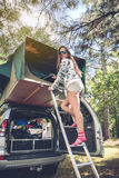 Woman standing in ladder opening tent over car Royalty Free Stock Photo