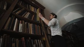 Woman standing on ladder taking book of bookshelf in old style library interior stock video footage
