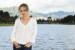 Woman standing beside a lake in Colombia. Young latin woman standing beside a lake at Simon Bolivar Central park in Bogot Stock Photo