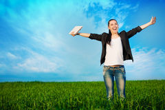 Woman standing with laptop on a green meadow Royalty Free Stock Photo