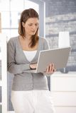 Woman standing with laptop at home Stock Images
