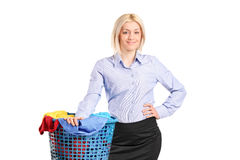 Woman standing by a laundry basket full of clothes Royalty Free Stock Image