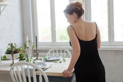 Woman standing and leaning on table Stock Images
