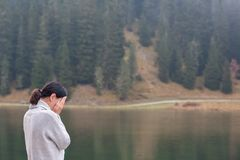 Young woman is standing lonely by the water and crying royalty free stock photography
