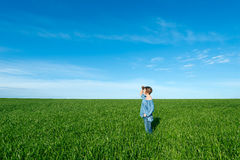 Woman standing and looking far away  in green field Royalty Free Stock Images