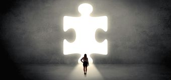Woman standing in front of a big puzzle piece stock photo