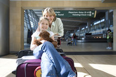 Woman standing beside luggage trolley in airport, daughter (7-9) sitting on suitcase with soft toy, smiling, front view, portrait Royalty Free Stock Images