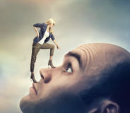 Woman standing on male face royalty free stock photography