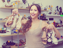 Woman standing with many shoes. Cheerful young woman standing in boutique with many chosen shoes in hands royalty free stock photography