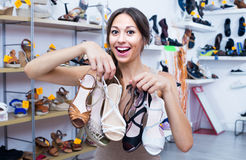 Woman standing with many shoes. Positive woman standing in boutique with many chosen shoes in hands royalty free stock photography