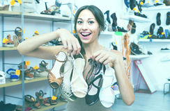 Woman standing with many shoes. Positive woman standing in boutique with many chosen shoes in hands stock image