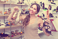 Woman standing with many shoes. Positive smiling woman standing in boutique with many chosen shoes in hands royalty free stock image