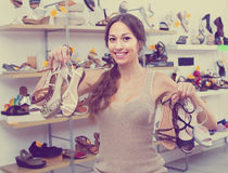 Woman standing with many shoes. Positive young woman 25-29 years old standing in boutique with many chosen shoes in hands royalty free stock photos