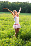 Woman is standing on meadow and her hands up Stock Photos