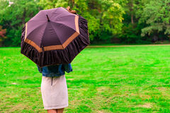 Woman standing in the meadow under the umbrella Royalty Free Stock Photo