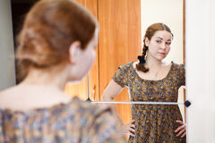 Woman standing before the mirror. Portrait of young Caucasian female in dress standing against mirror and looking at herself in domestic room Royalty Free Stock Photography