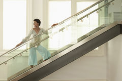 Woman Standing On Modern Glass Stairs. Happy young African American woman standing on modern glass stairs Royalty Free Stock Image