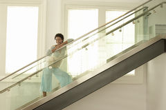 Woman Standing On Modern Glass Stairs. Happy young African American woman standing on modern glass stairs Stock Photo