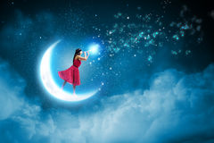 Woman standing on moon Stock Images