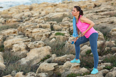 Woman standing after morning running on the rocks by the sea Stock Images
