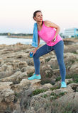 Woman standing after morning running on the rocks by the sea Stock Photography