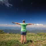 Woman standing on a mountain top Stock Photo