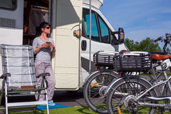 Woman is standing with a mug of coffee near the camper. Caravan car Vacation. Family vacation travel, holiday trip in motorhome Royalty Free Stock Images