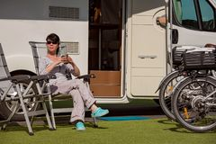 Woman is standing with a mug of coffee near the camper RV. Stock Photos