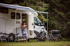 Woman is standing with a mug of coffee near the camper RV. Woman is standing with a mug of coffee near the camper. Caravan car Vacation. Family vacation travel stock photography
