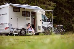 Woman is standing with a mug of coffee near the camper RV. Woman is standing with a mug of coffee near the camper. Caravan car Vacation. Family vacation travel royalty free stock photos